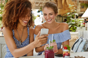 Positive young women recreat together at cozy restaurant, read good news online via cell phone, enjoy tasty cocktails or view funny photos from their excursion. Multiracial relationship concept