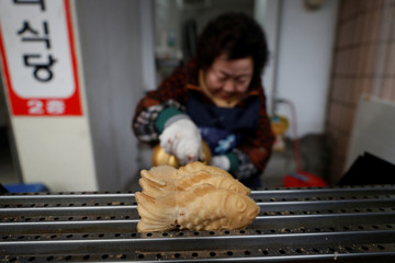 A woman cooks fish-shapes bread filled with sweet beans at the Jungang Market in Gangneung