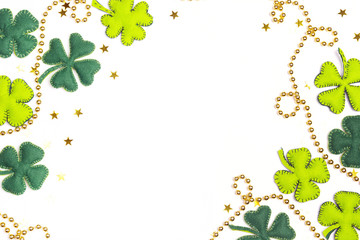 Frame of felt four-leaf clover and golden beads on white background. Space for text.