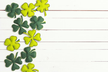 St.Patrick's day background with felt four-leaf clover on white wooden table. Space for text, top view.