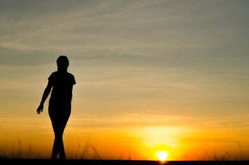 Woman silhouette is standing, raise one's hand for exercise, on evening .