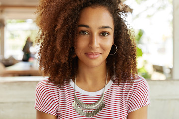 Photo of pretty African American female in striped t shirt, has positive expression, listens interlocutor who sits opposite her, spend dinner break at cafeteria. People, beauty and lifestyle concept