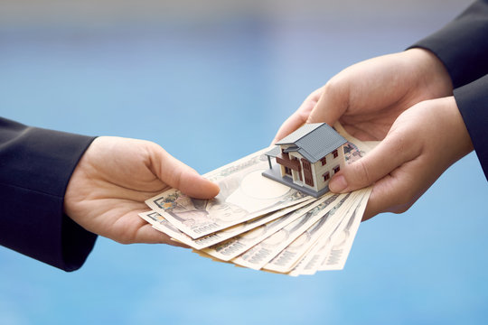 Two businessmen conduct a house sale with a model house and Yen banknotes valued at 10000 yen.using as background business concept and real estate concept with copy space for your text or design.