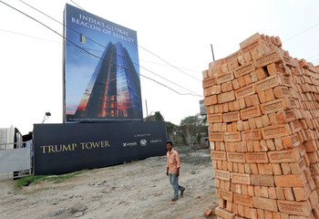 A man walks past a billboard of Trump Tower, a luxury apartment building, at a construction site in Kolkata