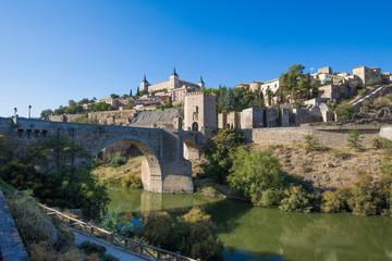 Shot from green water river Tagus, Tajo in Spanish, of Alcantara arch bridge and door,  landmark and monument from ancient Roman age, in Toledo city, Spain, Europe