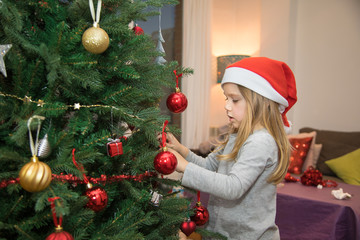 four years blonde cute child with red Santa Claus hat, decorating Christmas tree at home