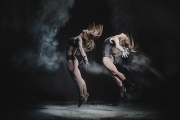 Two girls dance with flour on black background