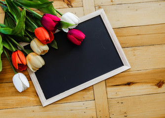 Colorful tulips on wooden table with blue empty chalk board, copy space area.Image for love and kindness concept.