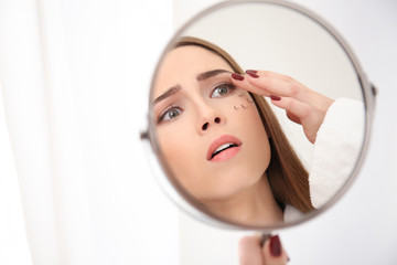 Young woman with eyelash loss problem looking at herself in mirror on light background