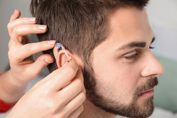 Doctor putting hearing aid in man's ear indoors