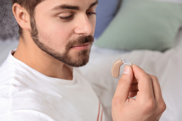 Young man holding hearing aid indoors