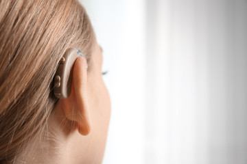Young woman with hearing aid indoors