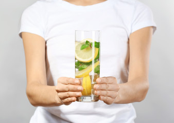 Young woman with glass of lemonade on grey background, closeup