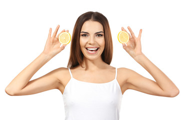 Beautiful young woman with slices of ripe lemon on white background