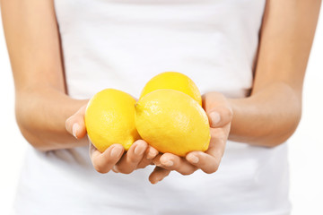 Young woman with ripe lemons, closeup