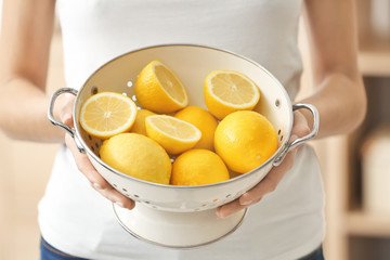 Young woman with colander full of ripe lemons, closeup