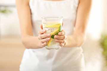 Young woman with glass of fresh lemonade, closeup