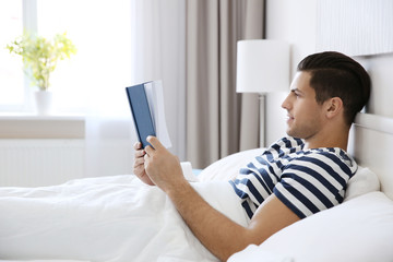 Young handsome man reading book in bed at home