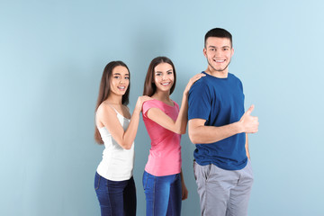 Young people posing together on color background. Unity concept