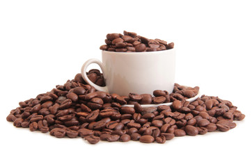 Coffee beans and a white cup on white background