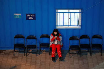A volunteer looks at her mobile phone at the PyeongChang 2018 Winter Olympic Park in Gangneung