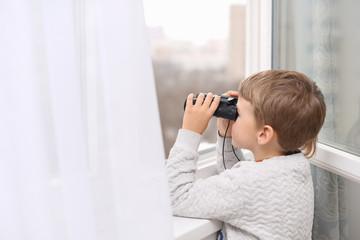 ittle boy looking through the window with binoculars