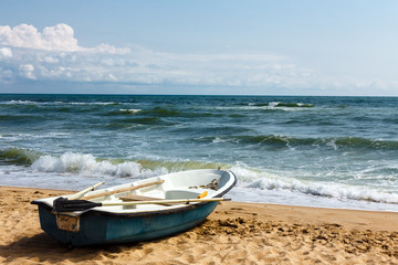 Old row boat on the sandy beach. Windy weather, waves in the sea bay