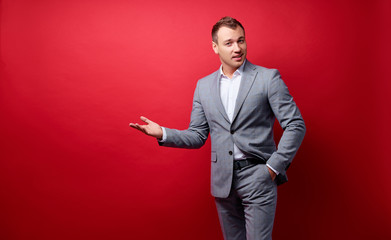 Advertisement. Colorful studio portrait of young handsome businessman pointing copy space. Red background.
