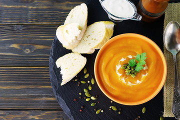 Pumpkin and carrot soup with cream and parsley on dark wooden background. Top view.  Copy space