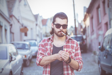Young man with cigarette posing on the street.