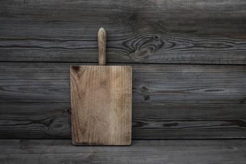 Old grunge wooden cutting board on dark background. Textured kitchen desk. Food concept .