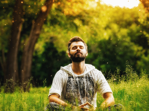 A bearded man meditating in the park