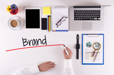 Business Concept: Businessman writing the words BRAND