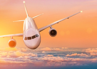 Airplane jetliner flying above clouds in beautiful sunset