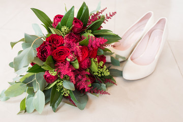Delicate, expensive, trendy bridal wedding bouquet of flowers in marsala and red color. Wedding bouquet with red roses and greenery in focus beige shoes on background. Wedding accessories.
