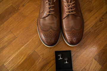 Men's accessories. Brown leather shoes and silver cufflinks in a box on a wooden background. Groom details