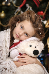 portrait of a little girl with a white toy bear at Christmas