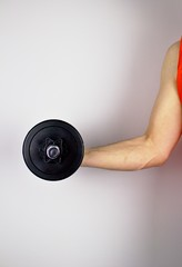 Young man practicing with a dumbbell.The man holds the dumbbell in his right hand and strengthens.