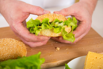 Close-up of a man's hands lth a vegetarian sandwich with cheese and green lettuce lettuce.