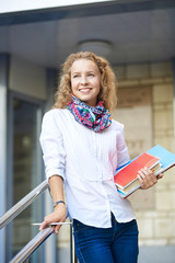 Smiling girl student standing on steps and holding folders