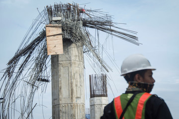 A worker stands near a collapsed girder pole on the construction site of the Bekasi-Cawang toll overpass in Jakarta
