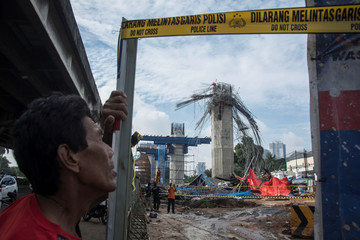 A man stands near a collapsed girder pole on the construction site of the Bekasi-Cawang toll overpass in Jakarta