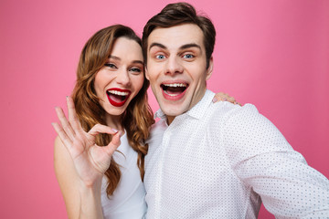 Portrait of joyful couple hugging and showing ok sign on camera while taking selfie, isolated over pink background