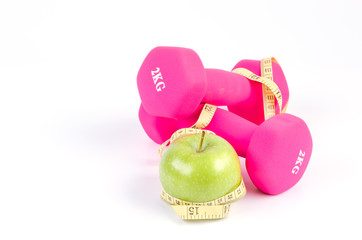 Dumbbells, fresh green apple and measure tape isolated on white background