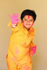 cute Indian boy celebrating Holi- the festival of colors