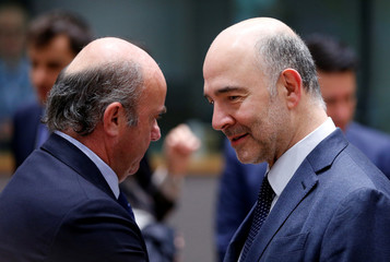 Spain's outgoing Economy Minister de Guindos listens to EU Commissioner Pierre Moscovici during a EU finance ministers meeting in Brussels