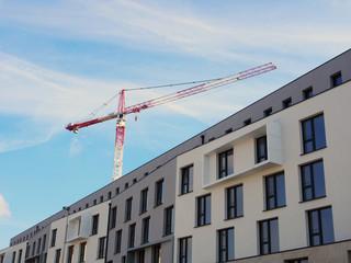Wohnungsbau: Neubaufassade mit Baukran