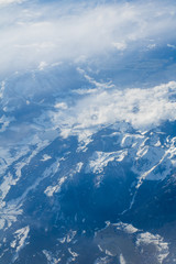 Snowy and cloudy scenic mountains scene from above