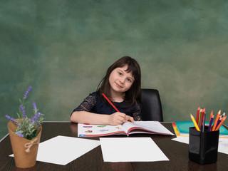 Brunette smilling child, sitting at desk. Portrait of happy girl, doing homework against green painted background. School concept