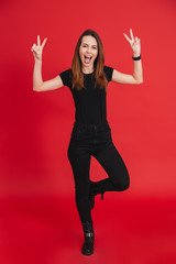 Full-length image of joyful woman in total black outfit posing on camera with smile and victory sign, isolated over red background